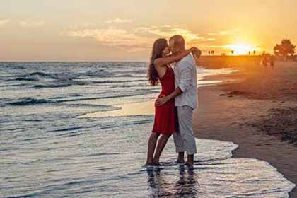 A photo of a couple hugging each other at the beach with the sun setting behind them